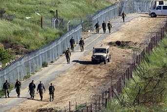 Israeli soldiers inspect the border fenc