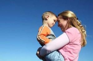 La mamma tiene affettuosamente in braccio il figlio.