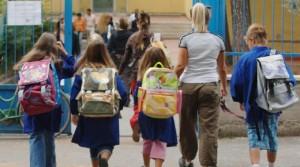 Bambini si recano a scuola con i genitori