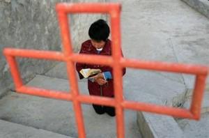 Cristiano coreano in preghiera davanti alla croce.