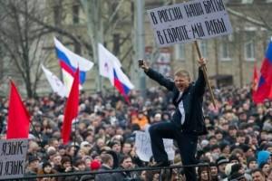 """Manifestante Pro-Russia a Donetsk con un cartello che dice: """"In Russia abbiamo fratelli, in Europa siamo schiavi""""."""
