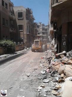 Escavatrici a lavoro per le strade di Homs.