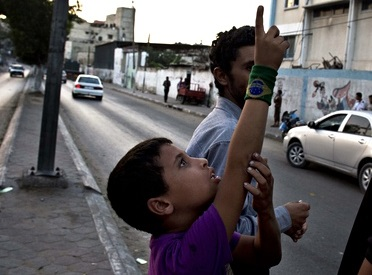 A Palestinian boy points to Israeli drones over Gaza City as eight days of relative calm ended