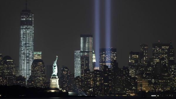 The Tribute in Light is illuminated next to the Statue of Liberty (C) and One World Trade Center (L) during events marking the 12th anniversary of the 9/11 attacks on the World Trade Center in New York, Sept. 10, 2013. Reuters