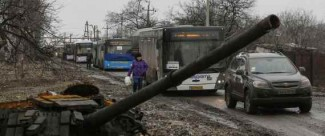Empty buses, intended for internally displaced persons (IDPs), wait along a road beside a burnt-out tank turret while travelling in the direction of the village of Debaltseve to evacuate the residents, in Vuhlehirsk, Donetsk region