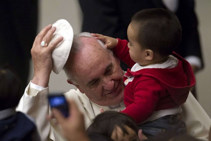 Pope Francis has his skull cap removed by a child during an audience with children assisted by volunteers of Santa Marta institute in Paul VI hall at the Vatican December 14, 2013. REUTERS/Giampiero Sposito (VATICAN - Tags: RELIGION TPX IMAGES OF THE DAY SOCIETY)