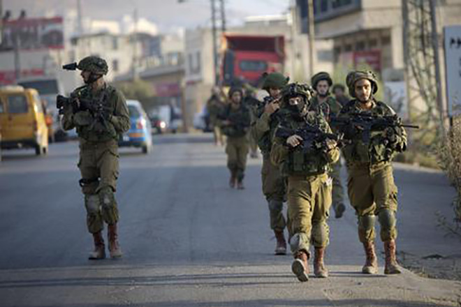 Israeli soldiers patrol during a search for the suspected Palestinian killers of two Jewish settlers in the West Bank city of Nablus, Saturday, Oct. 3, 2015. An Israeli couple was killed in a drive-by shooting driving on an West Bank road Thursday. (ANSA/AP Photo/Majdi Mohammed)