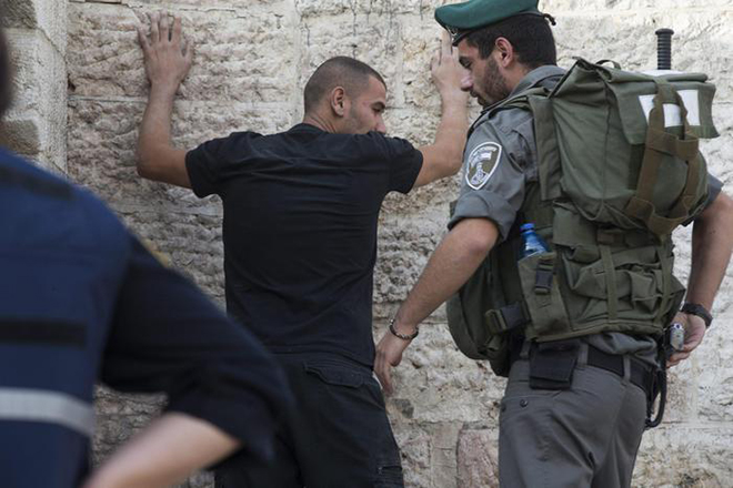 epa04976425 An Israeli policeman checks a Palestinian man at the Damascus Gate of the old city as security measures are increased in Jerusalem, Israel, 13 October 2015. The past 12 days have seen the worst spell of street violence in Israel and the Palestinian areas in years, stirred in part by Muslim anger over perceived changes to the status quo observed at a disputed Jerusalem holy site. Sixteen Palestinians from the West Bank and Jerusalem have been killed, but more than half of them have been attackers shot dead after or during attempts to stab Israelis. EPA/ATEF SAFADI