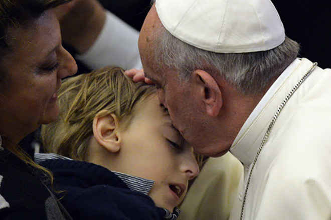 Pope Francis kisses a child during a meeting with blind and deaf people at Paul VI audience hall on March 29, 2014 at the Vatican. AFP PHOTO / ANDREAS SOLARO