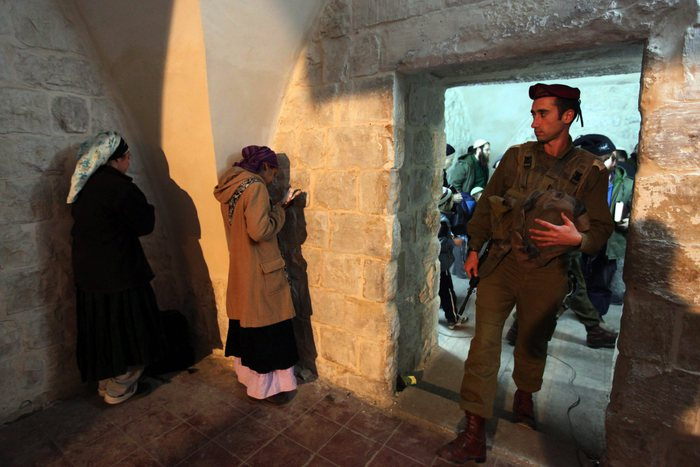 An Israeli soldier enters a room in the Joseph Tomb compound where ultra-Orthodox Jewish women are deep in prayer as hundreds of Jewish settlers and ultra-Orthodox Jewish pilgrims are escorted to Joseph's Tomb, in the West Bank city of Nablus early 28 December 2010. In coordination with the Palestinian forces that control Nabus, the Israeli army escorted hundreds of Jewish settlers to the ancient shrine, believed to be the final resting place of the biblical patriach. The tomb saw fierce fighting a decade ago in the 2nd Intifada and has recently undergone extensive renovations including a new roof. ANSA/KOBI GIDEON ISRAEL OUT