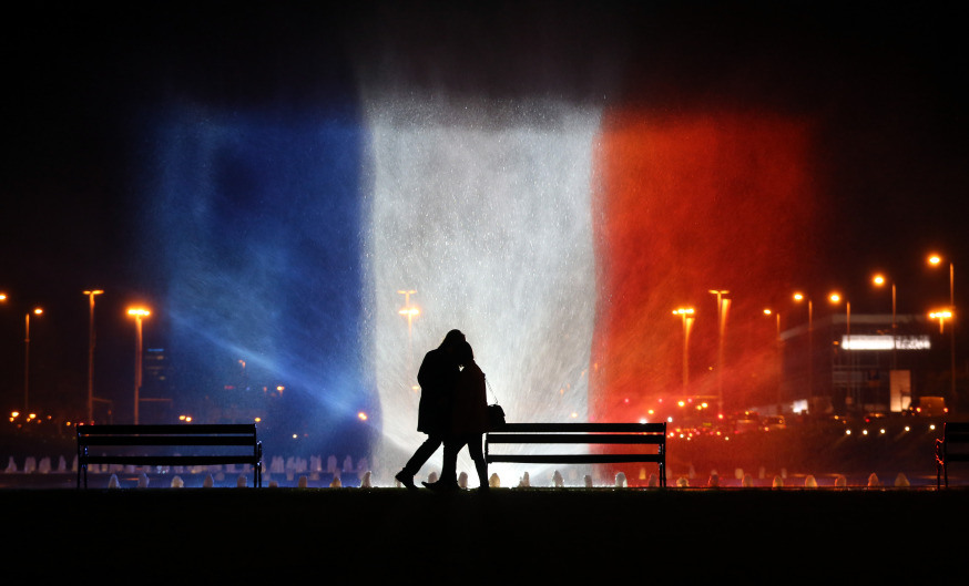 A young couple stands in front of illuminated waters with the colors of the French national flag on November 16, 2015 to pay tribute to victims of the attacks claimed by Islamic State which killed at least 129 people and left more than 350 injured on November 13. AFP PHOTO / STRINGER / AFP / STR