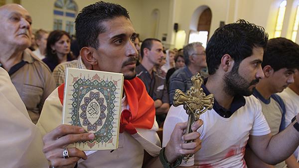 An Iraqi man carrying a cross and a Koran attends a mass at Mar Girgis Church in Baghdad