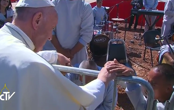 Al termine dell'incontro un momento di preghiera silenzioso con due carcerati che Papa Francesco tiene per mano