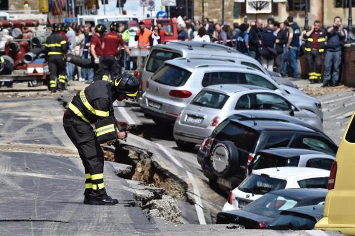 """The 200-metre-long hole opened up in a road running next to the Arno River in central Florence at about 6:30 local time on Wednesday, 25 May 2016. """"No one is injured, there's just damage - huge damage,"""" said Mayor Dario Nardella after arriving at the site on Lungarno Torrigiani, between Ponte Vecchio and Ponte alle Grazie bridges. ANSA/ MAURIZIO DEGL'INNOCENTI"""