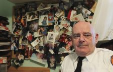 """In this Dec. 12, 2016 photo, Tim Jaccard sits in front of snapshots of some of the children who were safely relinquished under a """"Safe Haven"""" program he started 17 years ago, in Wantagh, N.Y. The retired ambulance medic lobbied legislatures across the country to pass so-called """"Safe Haven"""" laws in all 50 states. (AP Photo/Frank Eltman)"""