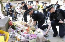 Police offices add to the flowers for the victims of Monday night pop concert explosion, in St Ann's Square, Manchester,  Tuesday May 23, 2017. A 23-year-old man was arrested in connection with Monday's Manchester concert bomb attack. The Islamic State group claimed responsibility Tuesday for the suicide attack at an Ariana Grande show that left over 20 people dead and dozens injured. ( Martin Rickett/PA via AP)