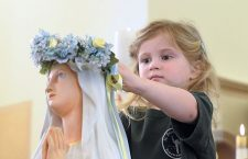20160506 - Three-year-old Lilly Colwell places a flower crown on the Blessed Virgin Mary as children from St. Francis of Assisi Early Childhood Center participate in a May Crowning at the church in Tonawanda. (Patrick McPartland/Staff Photographer)