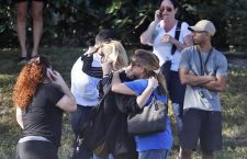 Anxious family members wait for news of students as two people embrace, Wednesday, Feb. 14, 2018, in Parkland, Fla. A shooting at Marjory Stoneman Douglas High School sent students rushing into the streets as SWAT team members swarmed in and locked down the building. (ANSA/AP Photo/Wilfredo Lee) [CopyrightNotice: Copyright 2018 The Associated Press. All rights reserved.]