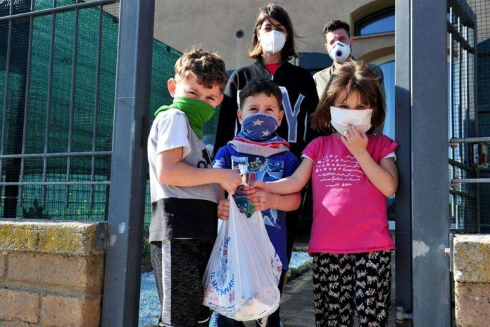 Una famiglia riceve aiuti da volontari - Reuters