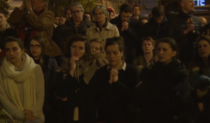 Fedeli pregano davanti Notre Dame che brucia